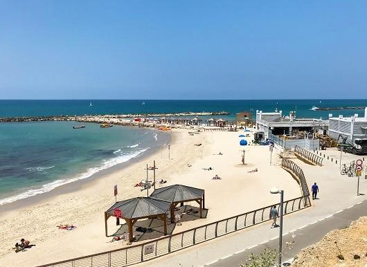 TEL AVIV, ISRAEL - MAY 15, 2018: The beach at the Tel Aviv Hilton Hotel. Sunbathers ejnoy a sunny day on the Mediterranean Sea.
